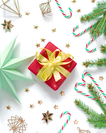 The gift wrapped in red wrapping paper is tied with a yellow ribbon with a bow. Natural spruce branches and holiday decorations are nearby. Christmas composition. Flat lay. Top view. Copy space.