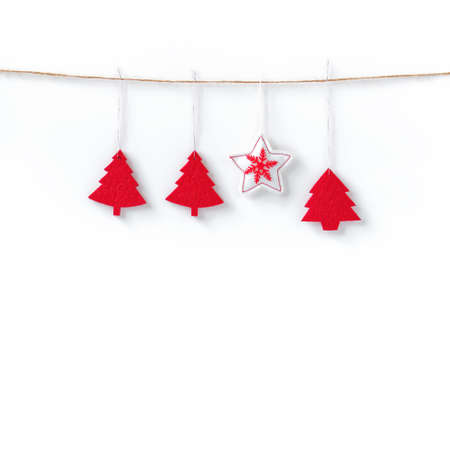 Red felt Christmas decorations tied to a rope on a white background. Christmas, New Year, winter concept. Flat lay. Top view. Copy space. Stock fotó