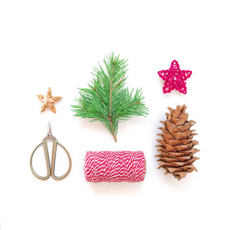 Christmas composition. A natural sprig of pine with green needles is on a white background. Nearby are a bump, a red and white rope, scissors, stars. Holiday preparation concept. Flat lay, top view.