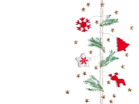 Christmas composition. Red felt decorations and green pine twigs are tied to a string. There are golden stars nearby. White background. New Year, winter concept. Flat lay. Top view. Copy space. Stock fotó