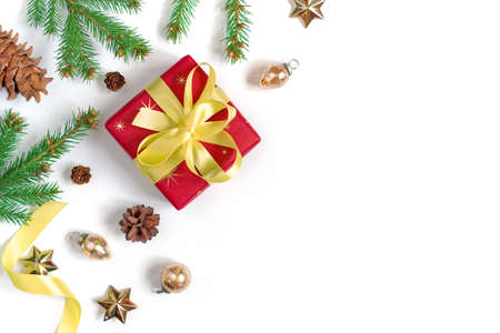 The gift wrapped in red wrapping paper is tied with a yellow ribbon with a bow. Natural spruce branch, cones and decorations are nearby. Christmas composition. Flat lay. Top view. Copy space. Stock fotó