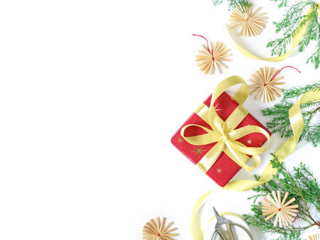Christmas layout. The gift wrapped in red wrapping paper is tied with a yellow ribbon with a bow. Nearby there are branches with green needles decorated with straw figures. Flat lay. Copy space. Stock fotó