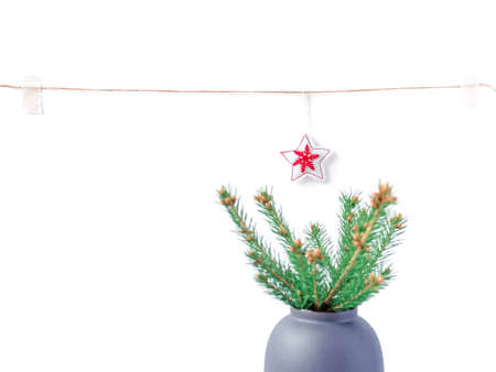 Christmas composition. A natural spruce branch with small cones is in a vase. In the background is a rope with ornaments hanging from it. New Year, winter concept. Greeting card. Stock fotó