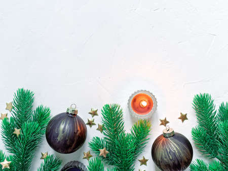 Christmas composition. Painted glass balls along with coniferous branches are on a light concrete background. Flat lay, top view, copy space.