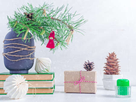 A natural pine branch decorated with an angel figurine is in a vase on a stack of books. Nearby are a gift wrapped in craft paper, paper pom-poms, a cedar cone and a candle. Christmas composition. Stock fotó