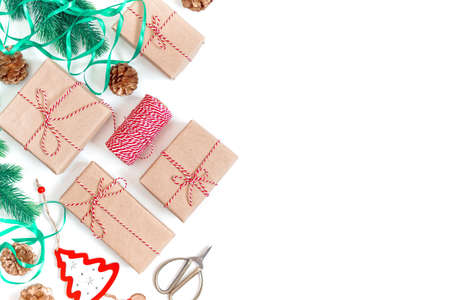 Christmas composition. Gifts in craft paper are tied with striped twine. Fir branches and festive decorations are nearby. White background. Flat lay. Top view. Copy space.