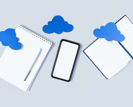 Cloud office concept, cloud sync. Smartphone with blank screen, open notebook with pen, diary (to-do list) are under a cloud on a gray background. Flat lay. Copy space.