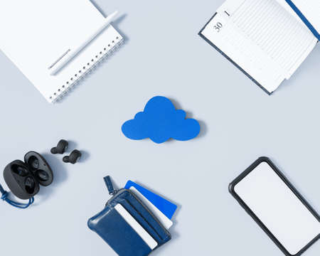 Cloud sync concept, office in the cloud. A blank screen smartphone, wireless headphones, a notepad with a pen, a to-do list and a wallet with credit cards are all around the cloud. Imagens