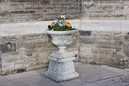 Stone vase with flowers by the brick wall of Casa Loma, Toronto photo