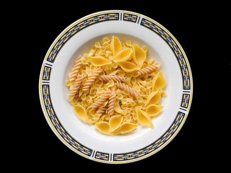 Yellow raw uncooked pasta and fusilli on a white plate with oriental ornament on a black background. Isolated. photo