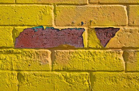 Lemon-yellow brick wall textured background, closeup, with red and green crack photo