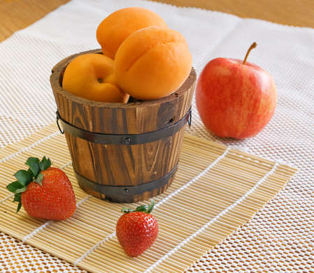 Yellow apricots in a wooden small bucket, red strawberries on a small bamboo mat. Red apple on a white background. Selective focus.