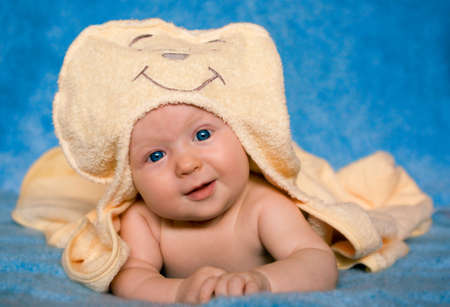 Closeup portrait of a cute smiling baby with blue eyes covered with a yellow blanket on a blue background. photo