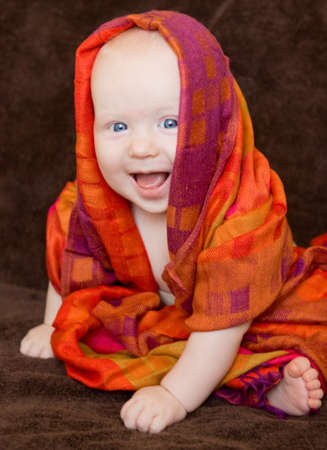 Cute smiling blond baby girl with blue eyes wrapped in a colorful shawl scarf on a brown background. photo