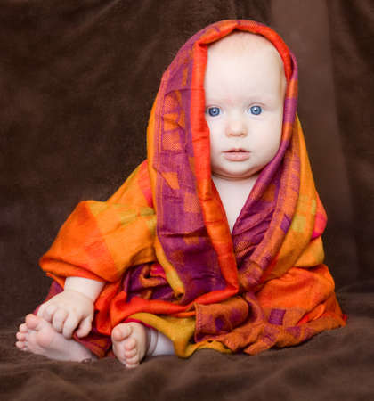 Cute serious blond baby girl with blue eyes wrapped in a colourful shawl scarf on a brown background. photo