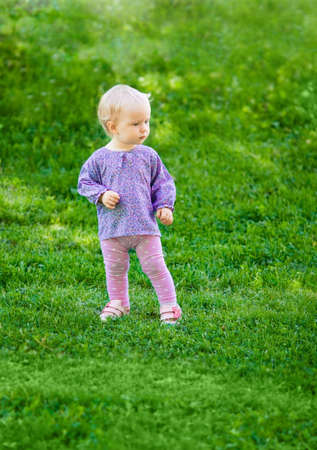 Adorable cute baby girl standing on a green meadow on a summer day. photo