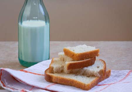 White rye loafs of bread and green bottle of milk. Plain rural breakfast. Selective focus.