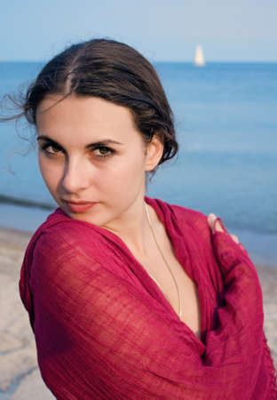 Closeup portrait of a young girl with a pink shawl on a beach near the water photo