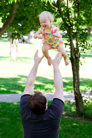 Father throwing daughter in the park. Smiling, laughing, summer photo