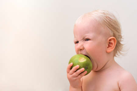 Closeup portrait of emotional baby eating apple. Angry, frustrated, aggressive.
