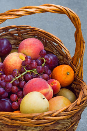Closeup still life of ripe purple grapes, red peach, orange tangerine and violet plums in a basket, summer, harvest photo