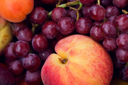 Closeup still life of ripe purple violet grapes, yellow apricot and red peach, summer, harvest photo