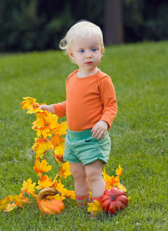 Portrait of a cute funny adorable blond Caucasian baby toddler with blue eyes in orange shirt and green shorts standing in the grass on the field meadow with yellow autumn fall leaves with pumpkins  Halloween card photo