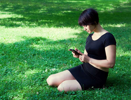 Portrait of a young lady girl woman with black short pixie haircut sitting on grass on field meadow on a sunny day in black tshirt and skirt with phone cell in her hand Banco de Imagens