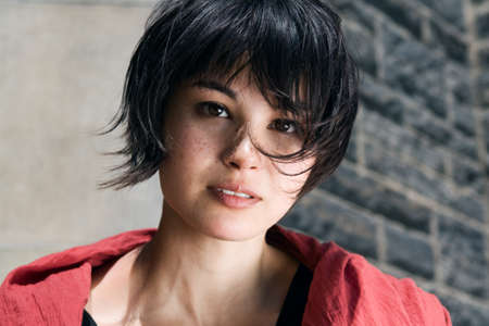 haircut: Closeup portrait of a beautiful young asian japanese girl woman with freckles with black short pixie haircut in red shawl scarf looking straight into the camera Stock Photo