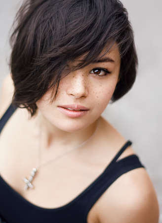 Closeup portrait of a beautiful young asian japanese girl woman with freckles, with black short pixie haircut looking into the camera  Selective focus