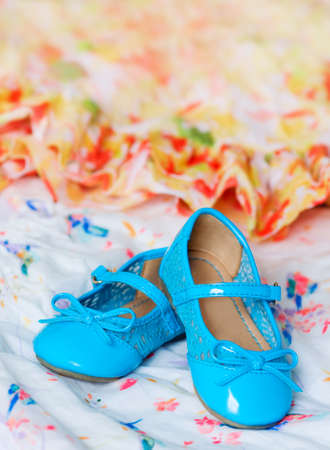 Pair of blue child s shoes on red and yellow dress with chiffon  Dancing, hobby, free time concept  Selective focus