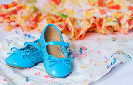 ruching: Pair of blue child s shoes on red and yellow dress with chiffon  Dancing, hobby, free time concept  Selective focus