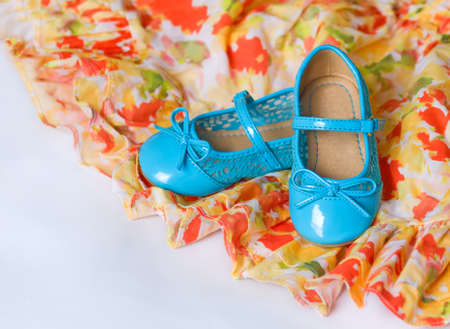 ruching: Pair of blue child`s shoes on red and yellow dress with chiffon. Dancing, hobby, free time concept. Selective focus. Card with copy space