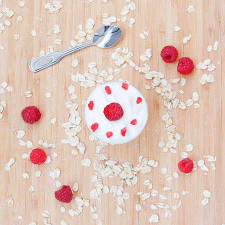 vibrant cottage: Tasty plain rustic dessert meal breakfast of raspberries with cream and oatmeals on a light wooden background with silver spoon