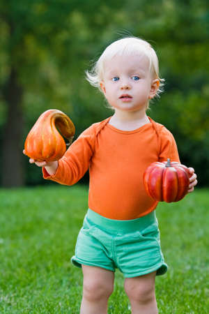 Portrait of a cute funny adorable blond Caucasian baby toddler with blue eyes in orange shirt and green shorts standing in the grass on the field meadow with pumpkins. Halloween card photo