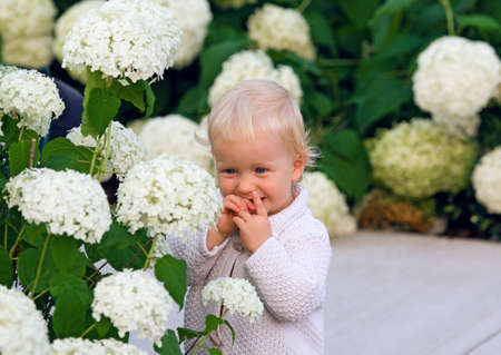 Cute adorable smiling baby child standing among flowers, lifestyle, happy childhood concept photo