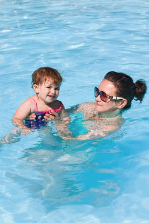 Mother and daughter playing in water in swimming pool on sunny summer day, training to swim, healthy lifestyle photo