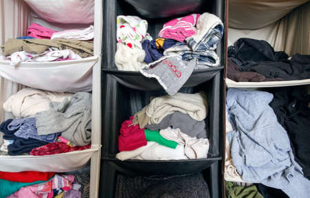 Messy untidy wardrobe closeup with colorful clothes for men, women, baby