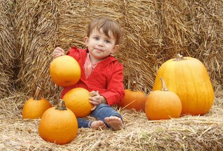 Retrato de un niño lindo divertido adorable sonriente caucásica bebé en la chaqueta roja y pantalones vaqueros azules que se sientan en el pajar en la granja con las calabazas. Tarjeta de Halloween de Acción de Gracias Foto de archivo - 33110685