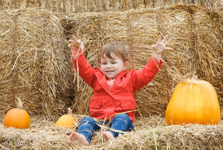 Portrait of a cute funny adorable smiling Caucasian baby toddler in red jacket and blue jeans sitting on the haystack on farm with pumpkins and playing with hay. Halloween Thanksgiving card photo