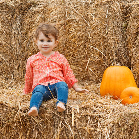 Portrait of a cute funny adorable smiling Caucasian baby toddler in red shirt and blue jeans sitting on the haystack on farm with pumpkins. Halloween Thanksgiving card photo