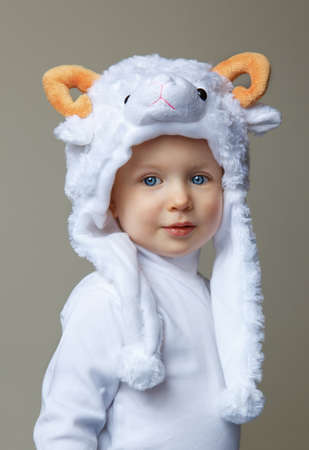 Cute adorable pretty Caucasian baby toddler with large blue eyes wearing a sheep hat hood with yellow horns on top and white shirt standing on a light background looking into the camera, New Year 2015 concept, studio photo