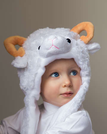 Closeup portrait of a cute adorable baby wearing a sheep hat hood with yellow horns and white shirt looking up on a light background, New Year 2015 concept, studio photo