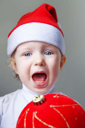 Closeup portrait of Caucasian baby with blue eyes wearing a Santa hat on light background holding red golden chinese ball decoration screaming in fear surprise, New Year concept photo