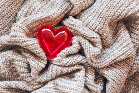 Closeup macro texture of knitted wool fabric material with lonely red shiny smooth heart on top, clothing background with wrinkles and folds, Valentine holiday love card Фото со стока - 36223891