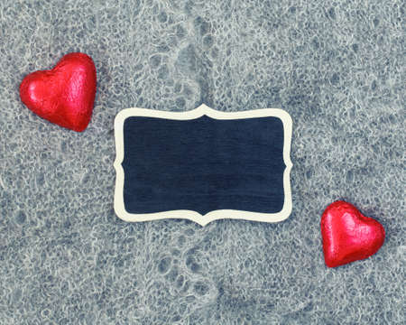 Closeup macro texture of knitted wool grey shawl with two red hearts and wooden plate board plaque with copyspace for text, Valentine holiday card, love retro vintage concept Фото со стока