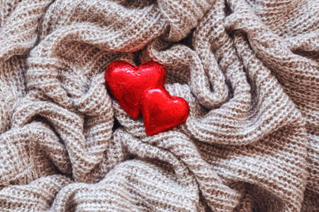 Closeup macro texture of knitted wool fabric material with red candy hearts on top, clothing background with wrinkles and folds, Valentine holiday card, love concept