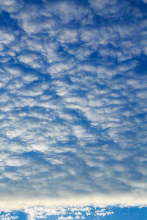 Dark heavy blue sky with small white clouds Stock Photo