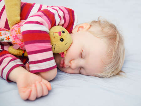 Closeup portrait of a cute adorable white blond Caucasian baby child toddler sleeping dreaming, lying on a bed with comforter toy, indoor Archivio Fotografico