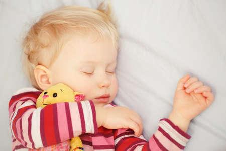 edred�n: Primer retrato de una adorable rubia blanca cauc�sica beb� ni�o ni�o dormido dreaming, acostado en una cama con el juguete consolador, cubierta Foto de archivo